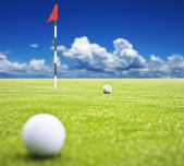 Golf ball on a putting green with the flag in the background - very shallow depth of field — Stock Photo