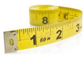 Mètre à ruban jaune sur enroulé sur fond blanc — Photo