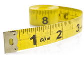 Yellow tape measure on rolled up on white background — Stock Photo