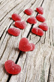 Red heart shaped jelly sweets on a rustic background — Stock Photo