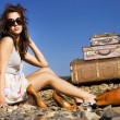 Stock Photo: Young traveling womwith her suitcases along road