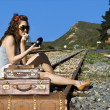 Royalty-Free Stock Photo: Young traveling woman with her suitcases on the railway tracks