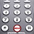 Keypad of a telephone with a red button for help - Stock Photo