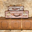 Three old leather suitcases on a grunge background — Stock Photo