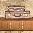 Stock Photo: Three old leather suitcases on grunge background