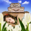 Traveling young woman resting in a tulip field with her suitcases - Stock Photo