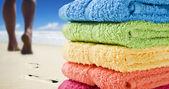 Kleurrijke handdoeken en iemand wandelen op het strand — Stockfoto