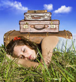 Traveling young woman resting in a field with her suitcases — Stock Photo
