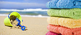 Colorful towels on a beach with toy bucket and spade — Stock Photo