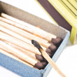Open box of matches with one match burning - Stock Photo