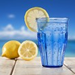 Stock Photo: Blue glass with sparkling water and lemon on wooden deck overlooking tropical beach - focus on lemon