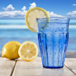A Blue glass with sparkling water and lemon on a wooden deck overlooking a tropical beach — Stock Photo