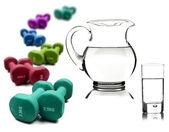 Estilo de vida saludable - agua en una jarra y cristal con mancuernas — Foto de Stock