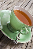 Green antique tea cup with healthy organic tea — Stock Photo