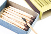 Open box of matches with one match burning — Stock Photo