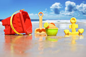 Closeup of children's beach toys at the beach - focus on watering can — Zdjęcie stockowe