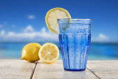 A Blue glass with sparkling water and lemon on a wooden deck overlooking a tropical beach - focus on the lemon — Stock Photo