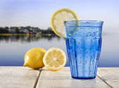 A Blue glass with sparkling water and lemon on a wooden deck overlooking the calm water of a tropical lagune — Stock Photo