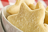 Sugar coated shortbread cookies in star shapes stacked up - on a white background with space for text — Stock Photo