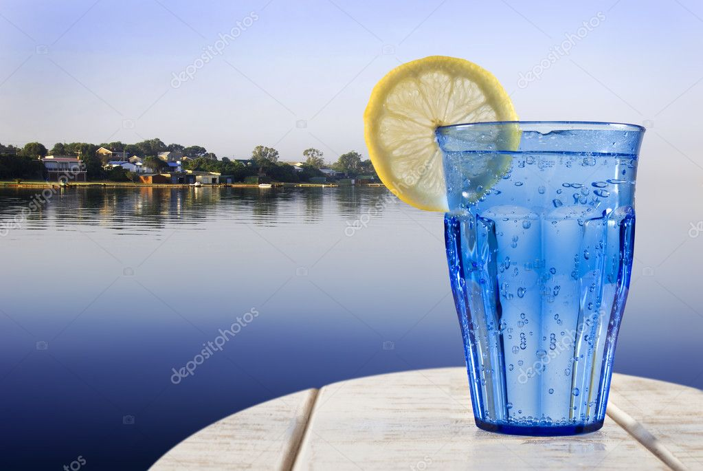 A Blue glass with sparkling water and lemon on a wooden deck overlooking the calm water of a tropical lagune — Stock Photo #10517139