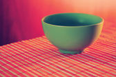 Green ceramic cup on a bamboo table cloth — Stock Photo
