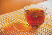 Cup of tea and fruit jelly on a bamboo table cloth — Photo