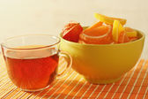 Cup of tea and fruit jelly with physalis on a bamboo table cloth — Stock Photo
