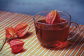 Cup of tea and physalis on a bamboo table cloth — Stock Photo