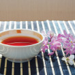 Stock Photo: Cup of teand cherry blossoms with lilac on bamboo table cloth