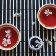 Two cups of tea, jar of teleaves and cherry blossoms on bamboo table cloth — Stock Photo #10531741
