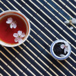 Cup of tea, jar of tea leaves and cherry blossoms on bamboo table cloth — Stock Photo