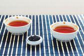 Taza de té y la jarra de té hojas en manteles de bambú — Foto de Stock