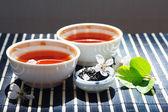 Deux tasses de thé, pot de feuilles de thé et de cerisiers en fleurs avec feuilles sur tissu de table en bambou — Photo