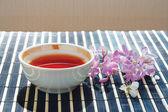 Taza de té y cerezo en flor con lila en mantel de bambú — Foto de Stock