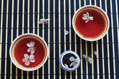 Two cups of tea, jar of tea leaves and cherry blossoms on bamboo table cloth — Stock Photo