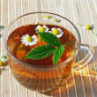 Cup of herbal tea with chamomile and green leaf — Stock Photo