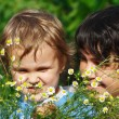 Young mom with her son among the summer daisies — ストック写真
