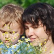 Foto Stock: Young mom with her son among the summer daisies