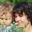 Young mom with her son among the summer daisies — Stock fotografie