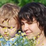 giovane mamma con suo figlio tra le margherite di estate — Foto Stock