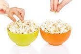 Hands of children eating popcorn — Stock Photo