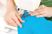 Hands of a seamstress at the sewing machine — Stock Photo