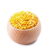Wooden bowl full of yellow split lentils isolated on white — Stock Photo