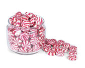 Glass jar full of red striped caramel sweets — Stock Photo
