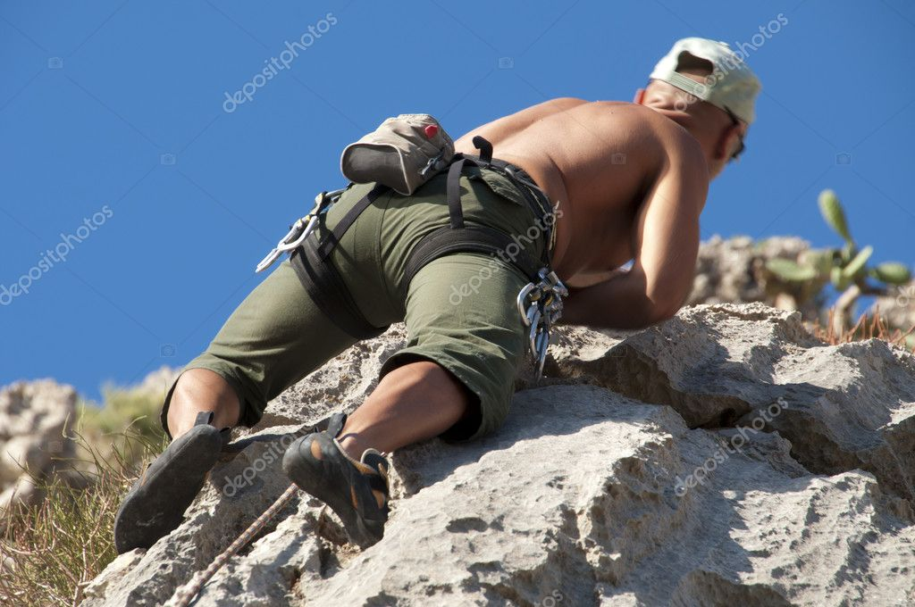 Climber while climbing a vertical rock wall — Stock Photo #8353189