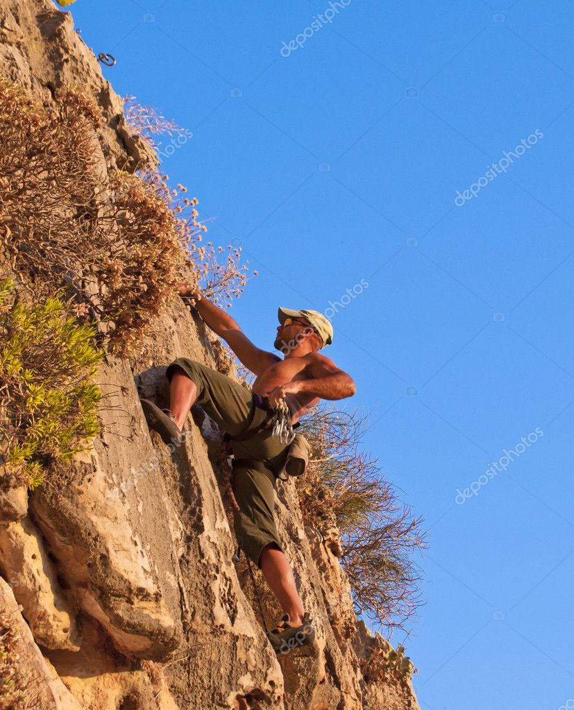 Climber while climbing a vertical rock wall  Stock Photo #8353245