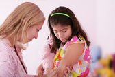 Doctor give injection to girl's arm, focus on the little girl. — Stock Photo