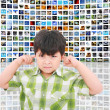 Kid protecting ears from loud noise of so many screens talking - Stock Photo