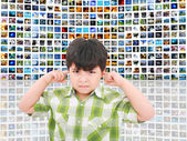 Kid protecting ears from loud noise of so many screens talking — Stock Photo