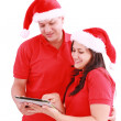 Happy Christmas couple looking a tablet computer. Isolated on wh — Stock Photo
